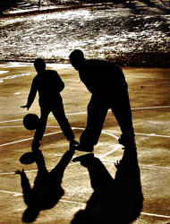 一位父亲与儿子在公园玩篮球