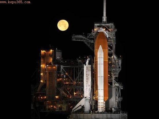 """佛罗里达州卡纳维拉尔角的肯尼迪航天中心,""""发现""""号航天飞机矗立在39A发射架上,即将发射升空。在航天飞机身后,一轮满月高悬于夜空之中。照片于2009年3月拍摄,""""发现""""号将执行STS-119任务"""