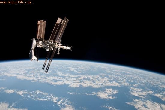 """2011年5月23日,""""奋进""""号航天飞机悬挂在国际空间站一端,这是它的最后一次太空任务。照片由附近""""联盟""""号飞船上的宇航员拍摄,是首批展现与空间站对接的航天飞机照片之一"""