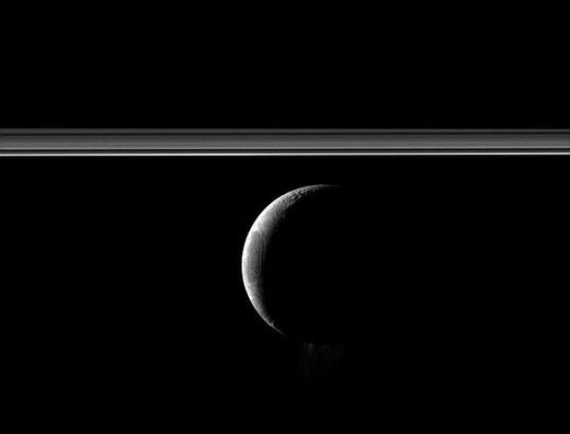 """在新月状土卫二底部的""""烟雾效应""""是环绕在土卫二周围冰水、灰尘和气体的类似间歇泉环状结构,它们有助于土星E环的形成"""