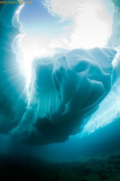 一块外形奇特的冰山浮在湖底,湖面闪现着阳光。