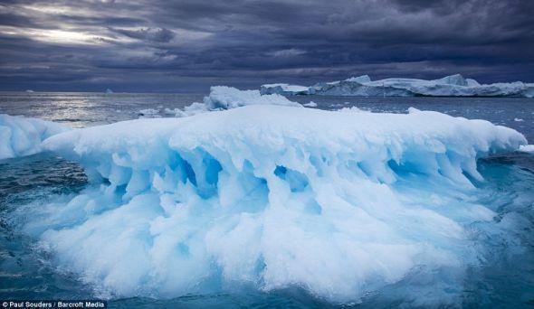 在格陵兰伊卢利萨特一个暴风雨大作的傍晚,一座正在融化的冰山漂浮在雅各布峡湾附近